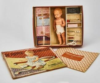 Puppen-Schneiderei: Kasten mit Puppe, Stoff und Schnittmuster zum Nähen von Puppenkleidern. Hersteller: Otto Maier, Ravensburg. 1950er-Jahre