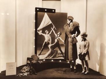 """Die passende Kleidung für wichtigen Anlässe. Mit dieser inszenierten Schaufensterauslage warb ein Kaufhaus auf 5th Avenue in New York City im Jahre 1936 für  seine Waren und den Besuch des Anti-Kriegsballetts """"Der Grüne Tisch"""" der Ballets Jooss."""